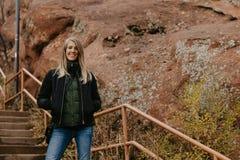 Giovane bella donna caucasica moderna che sorride mentre viaggiando al parco rosso delle rocce negli Stati Uniti fuori in natura  fotografie stock