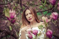 Giovane bella donna caucasica nel giardino di fioritura della molla delle magnolie La ragazza nel giardino un giorno nuvoloso Fotografie Stock