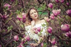 Giovane bella donna caucasica nel giardino di fioritura della molla delle magnolie La ragazza nel giardino un giorno nuvoloso Fotografia Stock