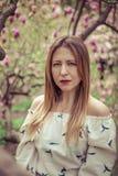 Giovane bella donna caucasica nel giardino di fioritura della molla delle magnolie La ragazza nel giardino un giorno nuvoloso Fotografia Stock Libera da Diritti