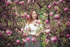 Giovane bella donna caucasica nel giardino di fioritura della molla delle magnolie La ragazza nel giardino un giorno nuvoloso Immagini Stock