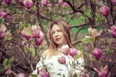 Giovane bella donna caucasica nel giardino di fioritura della molla delle magnolie La ragazza nel giardino un giorno nuvoloso Immagine Stock