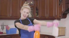 Giovane bella donna che alza le bottiglie del detersivo su, imbroglianti intorno Giorno di pulizia Lavoro domestico della famigli stock footage