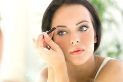 Giovane bella donna che applica eye-liner sulla palpebra con la spazzola Immagine Stock Libera da Diritti