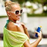 Giovane bella donna che applica la lozione protettiva del sole sulla spalla immagini stock libere da diritti