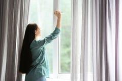 Giovane bella donna che apre grande finestra immagine stock libera da diritti