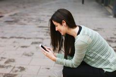 Giovane bella donna che ascolta la musica con il telefono dentro all'aperto Fotografia Stock