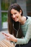 Giovane bella donna che ascolta la musica con il telefono dentro all'aperto Immagini Stock