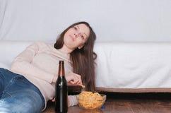 Giovane bella donna che beve una birra e che mangia i chip che mettono sul pavimento vicino allo strato Sorridere e sognare circa Fotografia Stock Libera da Diritti
