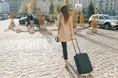 Giovane bella donna che cammina lungo la via della città con la valigia ed il telefono cellulare di viaggio Ragazza castana alla  fotografie stock libere da diritti