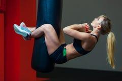 Giovane bella donna che fa addestramento funzionale del crossfit di allenamento dell'ABS sul punching ball Forte ragazza sportiva Fotografia Stock