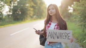 Giovane bella donna che fa auto-stop condizione sulla strada che tiene dovunque segno e che per mezzo dello smartphone Ritratto c video d archivio