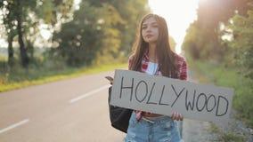 Giovane bella donna che fa auto-stop condizione sulla strada che tiene il segno di Hollywood e che per mezzo dello smartphone Rit video d archivio