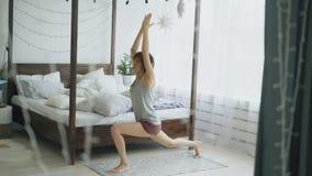 Giovane bella donna che fa esercizio di yoga vicino al letto in camera da letto a casa fotografia stock