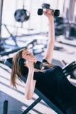 Giovane bella donna che fa gli esercizi con la testa di legno in palestra Immagine Stock Libera da Diritti