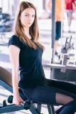 Giovane bella donna che fa gli esercizi con la testa di legno in palestra Fotografia Stock Libera da Diritti