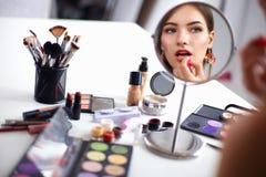 Giovane bella donna che fa trucco vicino allo specchio, sedentesi allo scrittorio Immagini Stock Libere da Diritti