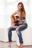 Giovane bella donna che gioca chitarra Fotografia Stock