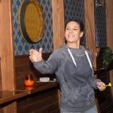 Giovane bella donna che gioca i dardi in un club Fotografia Stock