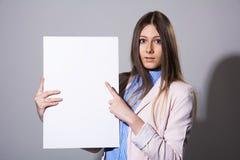 Giovane bella donna che indica ad un foglio bianco Fotografie Stock Libere da Diritti