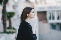 Giovane bella donna che indossa i vestiti neri totali che stanno sull'argine della città Fotografia Stock