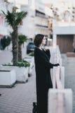 Giovane bella donna che indossa i vestiti neri totali che stanno sull'argine della città Immagini Stock