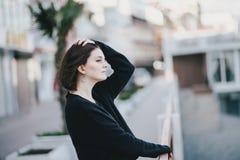 Giovane bella donna che indossa i vestiti neri totali che stanno sull'argine della città Immagine Stock