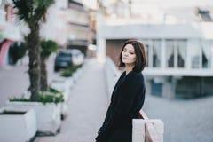 Giovane bella donna che indossa i vestiti neri totali che stanno sull'argine della città Immagine Stock Libera da Diritti