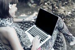Giovane bella donna che lavora con il computer portatile al parco tropicale all'aperto, al sorriso ed a ritenere di rilassamento  Fotografia Stock