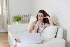Giovane bella donna che lavora con sorridere del computer portatile felice o fare spesa online di Internet Immagine Stock
