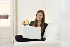 Giovane bella donna che lavora con sorridere del computer portatile felice o fare spesa online di Internet Fotografie Stock Libere da Diritti