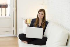 Giovane bella donna che lavora con sorridere del computer portatile felice o fare spesa online di Internet Fotografie Stock