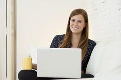 Giovane bella donna che lavora con sorridere del computer portatile felice o fare spesa online di Internet Immagine Stock Libera da Diritti