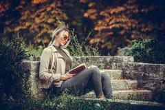 Giovane bella donna che legge un libro Fotografia Stock Libera da Diritti