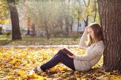 Giovane bella donna che legge un libro al parco Fotografie Stock