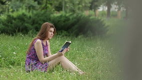 Giovane bella donna che legge un libro in natura stock footage