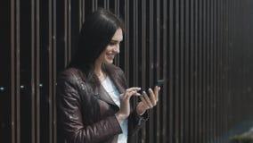Giovane bella donna che manda un sms sullo smartphone all'aperto archivi video