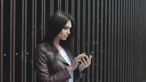 Giovane bella donna che manda un sms sullo smartphone nella città archivi video