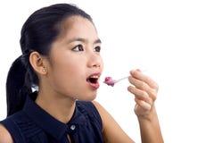 Giovane bella donna che mangia yogurt Immagini Stock