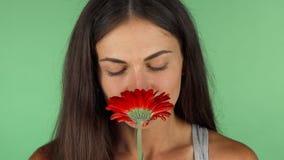 Giovane bella donna che odora fiore rosso sul fondo di verde di chromakey stock footage