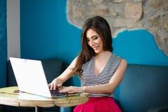 Giovane bella donna che per mezzo del computer portatile Immagini Stock