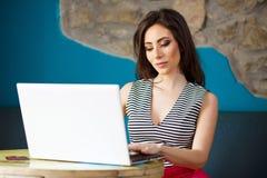 Giovane bella donna che per mezzo del computer portatile Fotografia Stock Libera da Diritti
