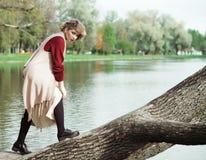 Giovane bella donna che posa su un albero fotografie stock libere da diritti