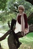 Giovane bella donna che posa su un albero fotografia stock libera da diritti