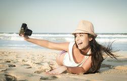 Giovane bella donna che prende le foto sulla spiaggia Fotografia Stock