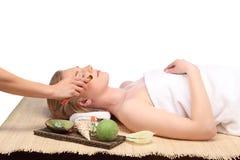 Giovane bella donna che riceve trattamento facciale della stazione termale e di massaggio immagine stock