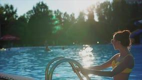 Giovane bella donna che scala la scala nella piscina sunlight archivi video