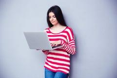 Giovane bella donna che scrive sul computer portatile Immagini Stock