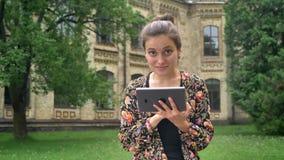 Giovane bella donna che scrive sulla compressa e che si siede sul banco vicino all'università in parco con erba, sorridente alla  archivi video