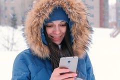 Giovane bella donna che scrive un messaggio a macchina sul suo telefono cellulare, quindi esaminante macchina fotografica e sorri fotografia stock